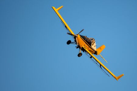 Yellow Crop Dusting Plane Flying in a Blue Sky Banco de Imagens