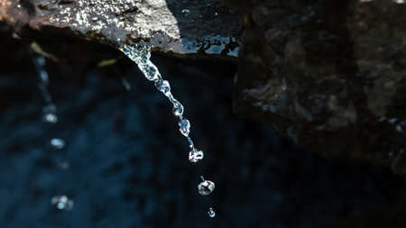 Silver Stream of Water Pouring from a Rock
