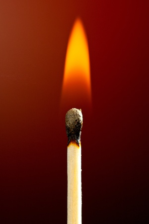 lighter: an inflamed match against a red background Stock Photo
