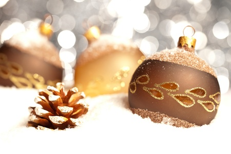 pinecone: three golden brown christmas balls on snow background with bokeh