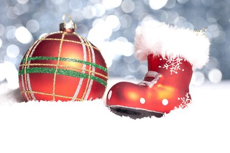 a red christmas ball on snow boots with christmas with bokeh background Stock Photo - 11223219