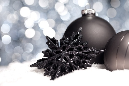 snow flowers: two black christmas balls with christmas star on snow with bokeh background Stock Photo