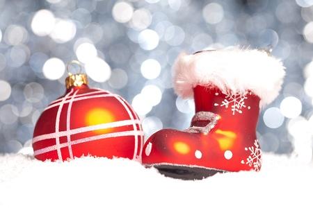botas de navidad: una bola roja de la Navidad en la nieve con botas de navidad con fondo bokeh Foto de archivo