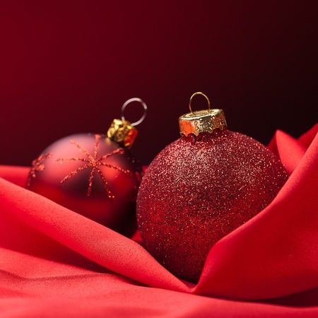 two red christmas balls on a red silk cloth photo