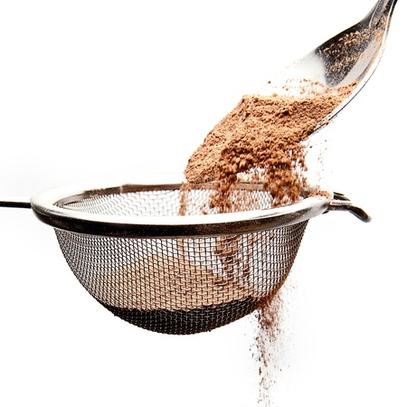 cocoa powder with a sieve and spoon photo