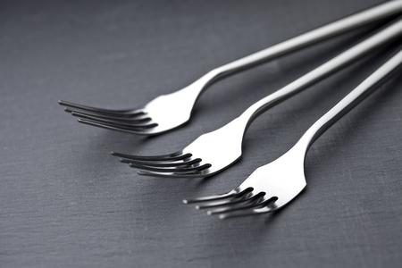three forks on a slate plate photo