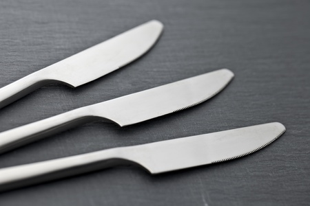 three knives on a slate plate photo
