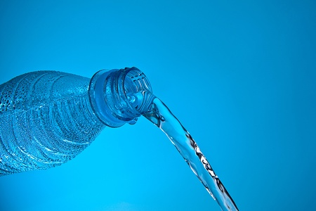 quencher: Water bottle in front of blue background