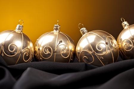 shafts: four golden christmas balls on silk Stock Photo