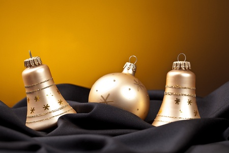 three golden christmas balls on black silk Stock Photo - 11337405