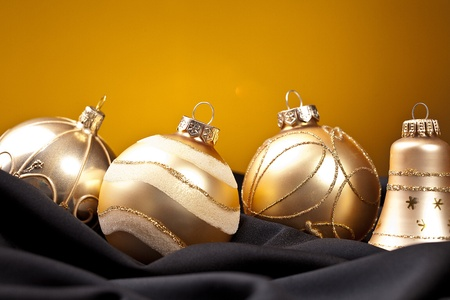 four golden christmas balls on black silk photo