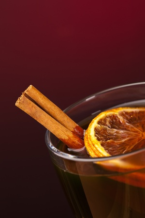 glass of mulled wine with cinnamon, lemon and anise photo