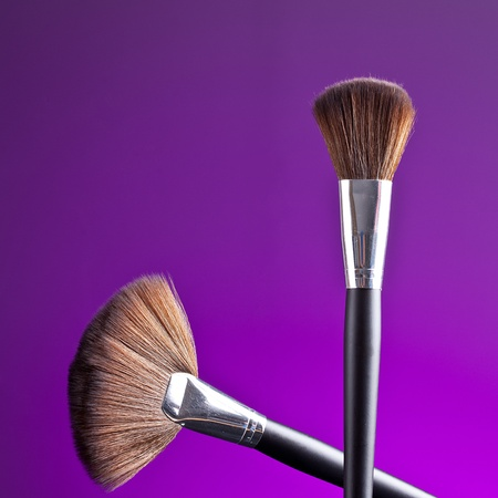 Powder brush against purple background photo