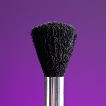 Powder brush against purple background photo