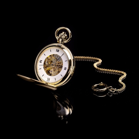 gold watch: Gold pocket watch on a black background