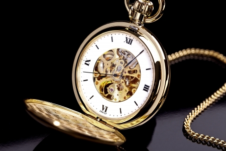 Gold pocket watch on a black background