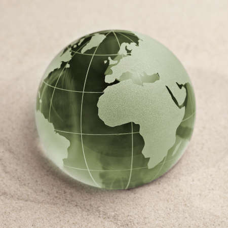 biologically: Green Glass globe on sand background Stock Photo
