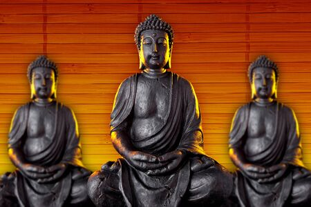 Buddha statue with glow against bamboo background photo