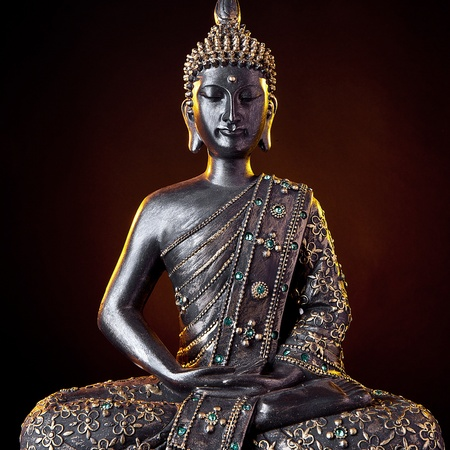Buddha statue with glow against black background photo