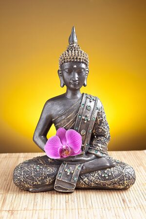 Buddha statue with orchid against golden background photo