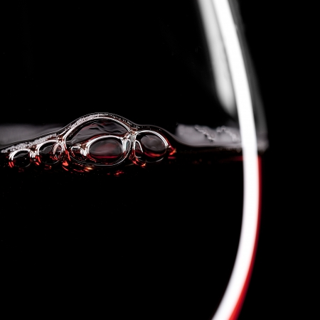 burgundy drink glass: Red Wine Glas silhouette with Bubbels on Black Background