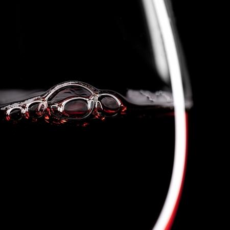 weinverkostung: Rotwein Glas Silhouette mit Bubbels auf schwarzem Hintergrund