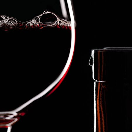 bottleneck: Red Wine Glas silhouette on Black Background with Bubbels and bottleneck with a drop   Stock Photo