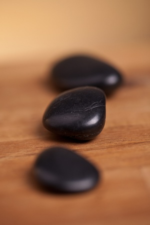 black stones on wood background Stock Photo - 12494480