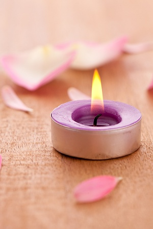 Rose leafs with candel on wooden background photo