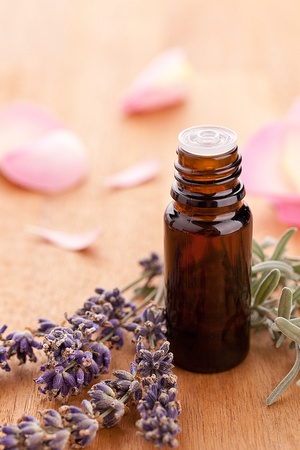 sense of security: lavendel and parfum bottle with rose leafs on wooden background