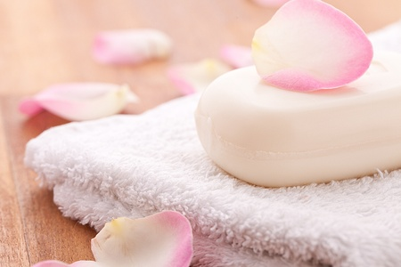 repelling: soap with rose leafs on towel and wooden background Stock Photo