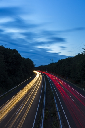 streaks: long time exposure freeway cruising car light trails streaks of light highway electricity pylon sky Stock Photo