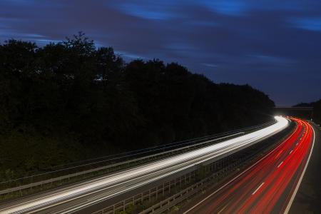 night traffic: long time exposure freeway cruising car light trails streaks of light speed highway blue hour sky