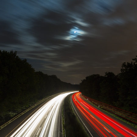 long time exposure freeway cruising car light trails streaks of light speed highway moon clouds photo