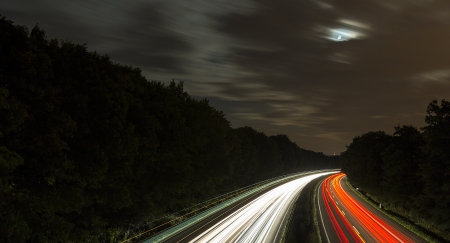 long time exposure freeway cruising car light trails streaks of light speed highway moon clouds Stock Photo