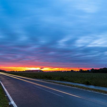 morning blue hour: sunrise clouds long exposure car car sunlight dusk red sky blue hour Stock Photo