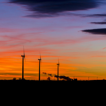 Sunrise wind farm windmill wind turbine winter energy Silhouette natural orange sunlight photo