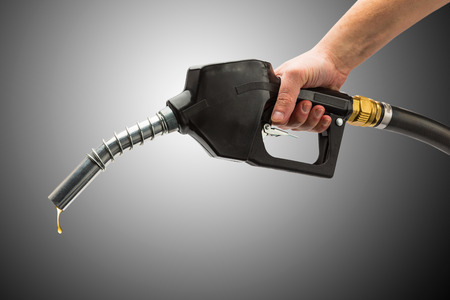 surtidor de gasolina: boquilla de la bomba de gasolina con gotas de gas de oro Foto de archivo