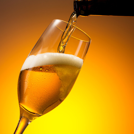 beer tulip: glass of cold beer with dew drops pouring out of a bottle Stock Photo