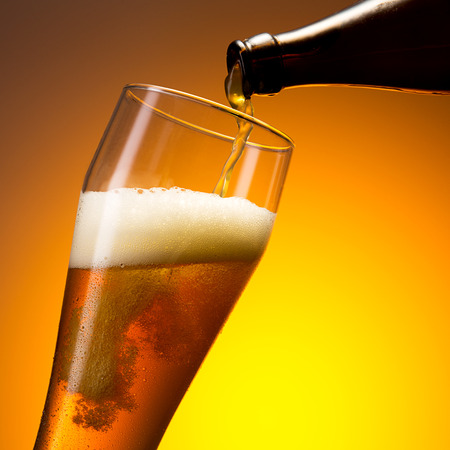 wheat beer: Pouring beer in to a cold glass with dew drops on orange background Stock Photo