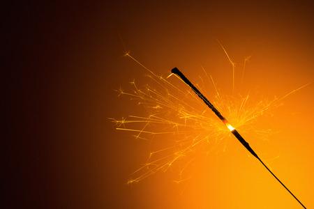 silvester: sparkler is burned for silvester on orange background