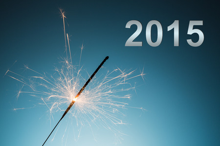 christmas profits: A sparkler for new years eve 2015 on blue background.