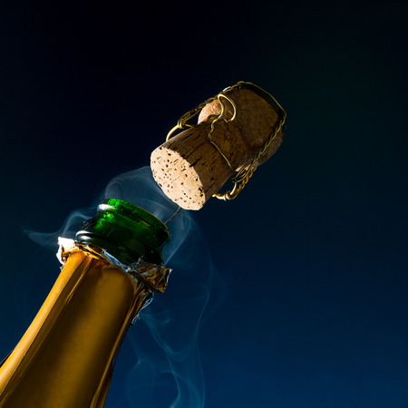 bottle of champagne with popping cork an steam