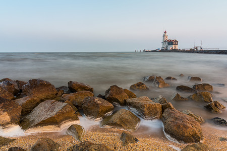 vuurtoren bij een steenachtige kust in Marken Nederland