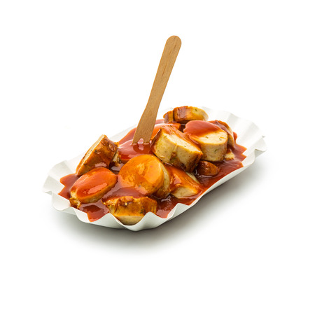 sliced currywurst in a papershell with wooden fork