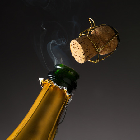 champagne bottle with popping cork on new years eve