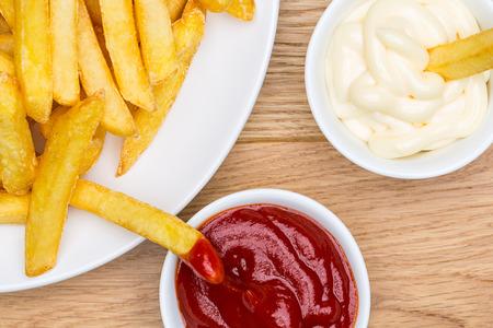 Teller mit Pommes frites mit Mayonnaise und Ketchup