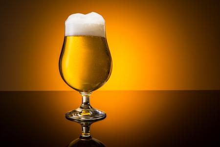 beer tulip: german beer in a tulip glass on orange background Stock Photo