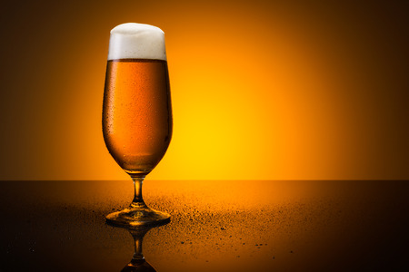 froth: glass of beer with froth crown and dew drops on orange sunset background Stock Photo