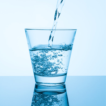 glass with pouring mineral water